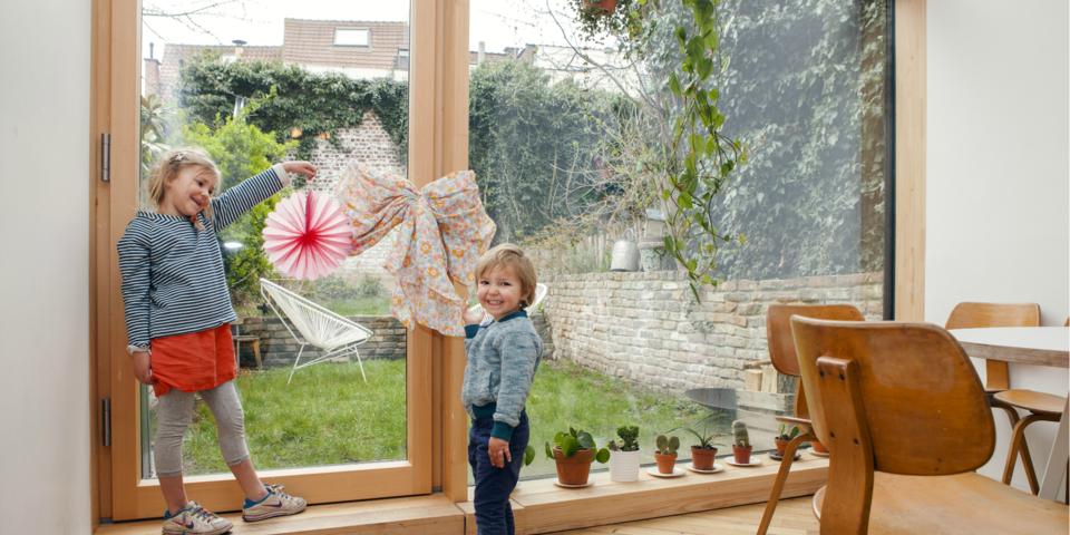 Twee kinderen staan voor een houten raam en houden een strik vast.