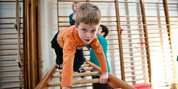 Leerling klimt over een bewegingsparcours