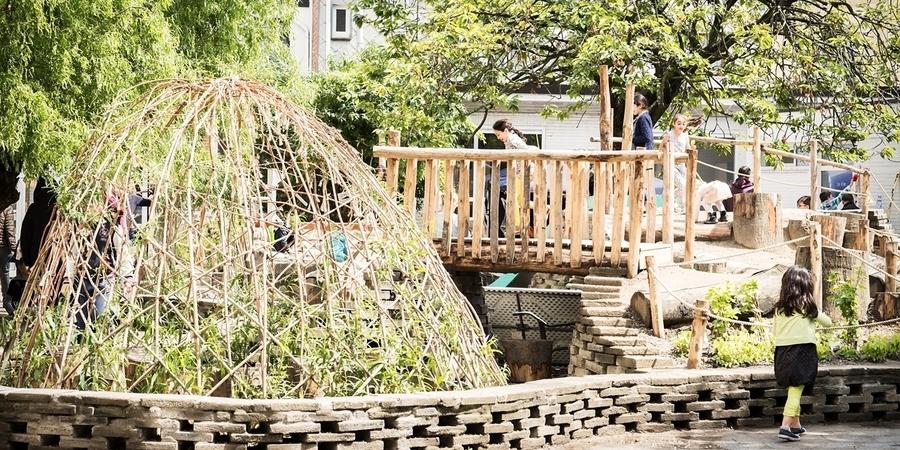 Groene speelplaats met wilgenhut en bruggetje