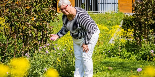 Vrouw bekijkt haar verschillende planten in de tuin