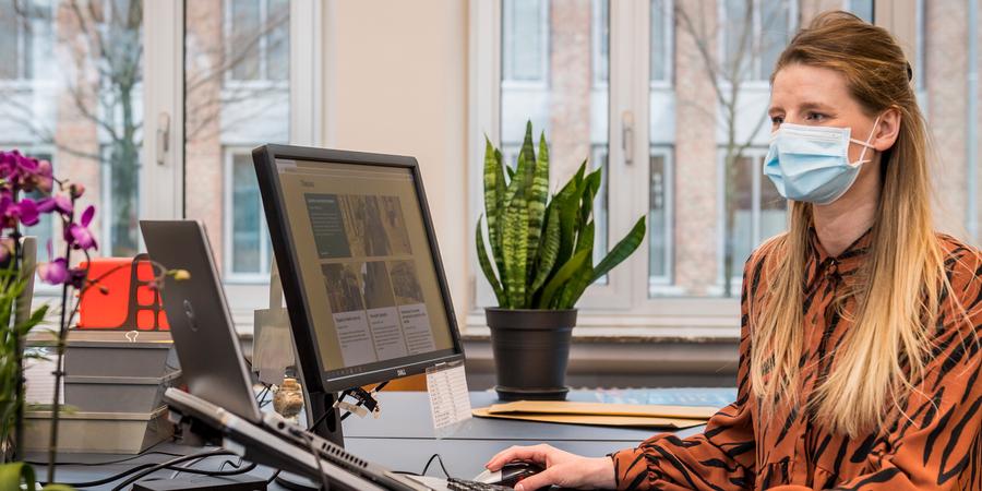 Dame achter laptop in kantoorsetting