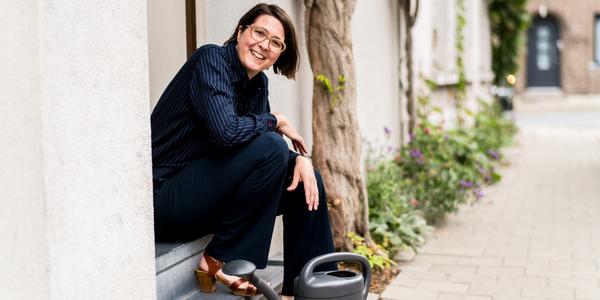 Foto van Borgerhoutenaar met gieter en geveltuintje aan haar voordeur