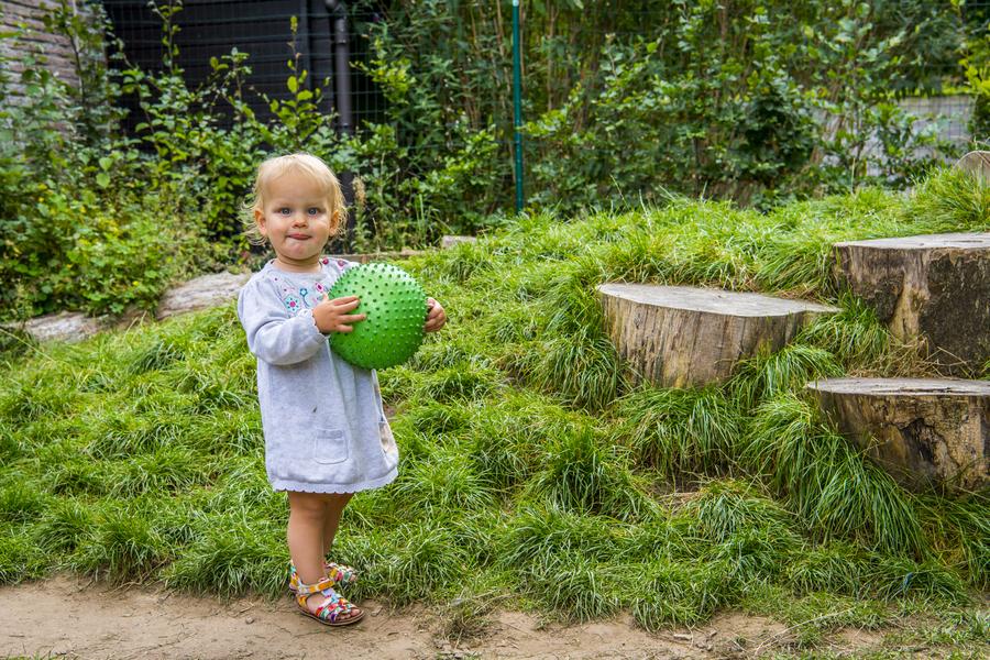 Meisje met bal staat bij de speelheuvel