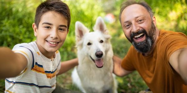 Vader en zoon nemen selfie met Zwitserse witte herdershond