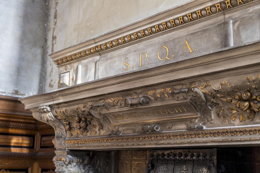 Gerestaureerde monumentale haard met gouden opschriften 'S.P.Q.A' en 'Recht en plicht'