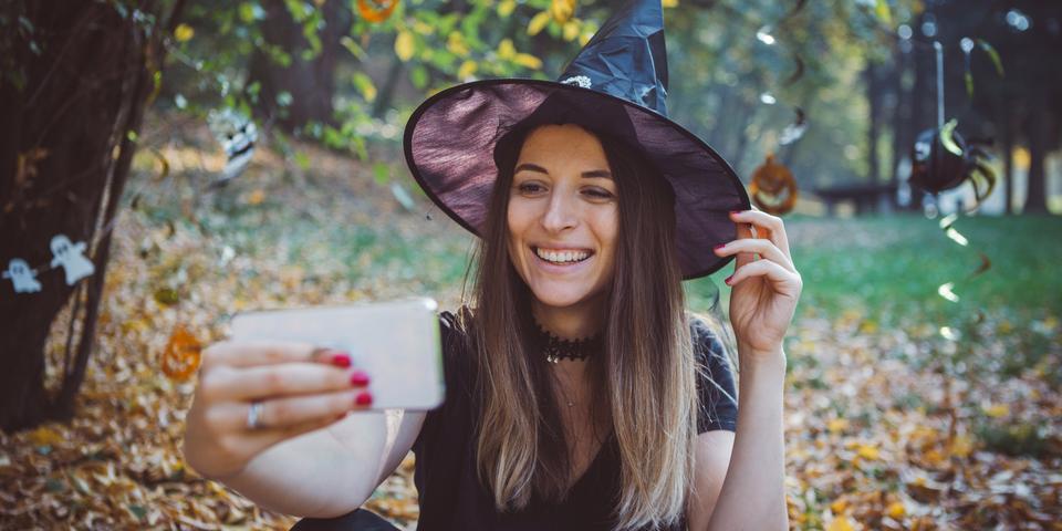 vrouw neemt selfie in het bos bij een Halloween-attribuut