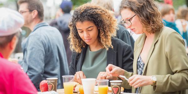 2 jongeren genieten genieten van hapje en drankje tijdens event