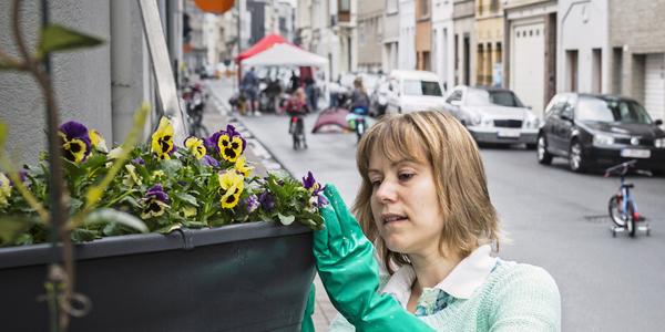 Buurtbewoonster tijdens Lentepoets met buurtfeest op de achtergrond