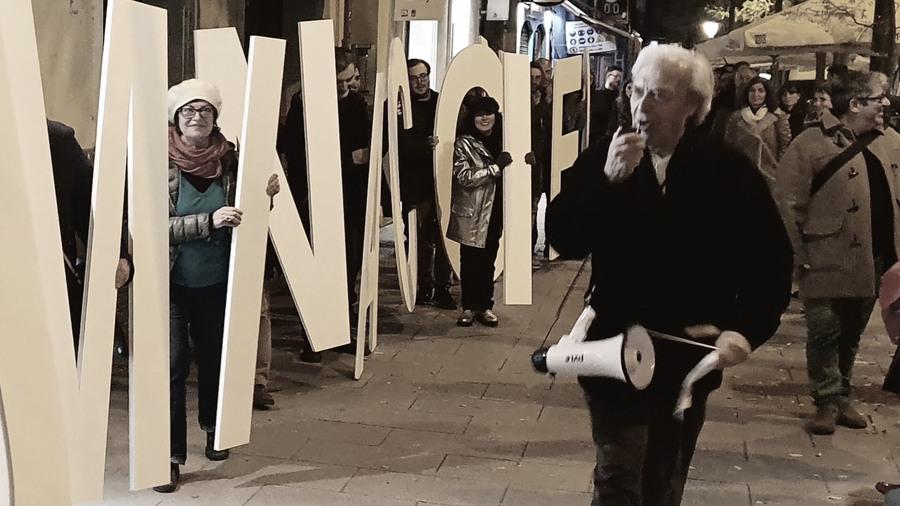 Man met megafoon en mensen met gigantische letters op straat