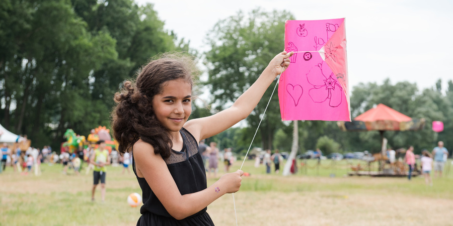 Meisje poseert met roze vlieger