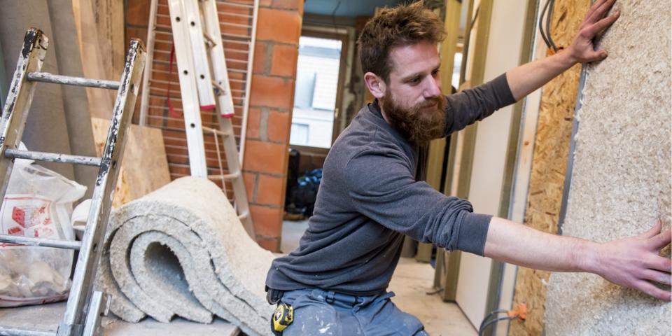 Een man op een bouwwerf plaatst nieuwe isolatie in de muur.