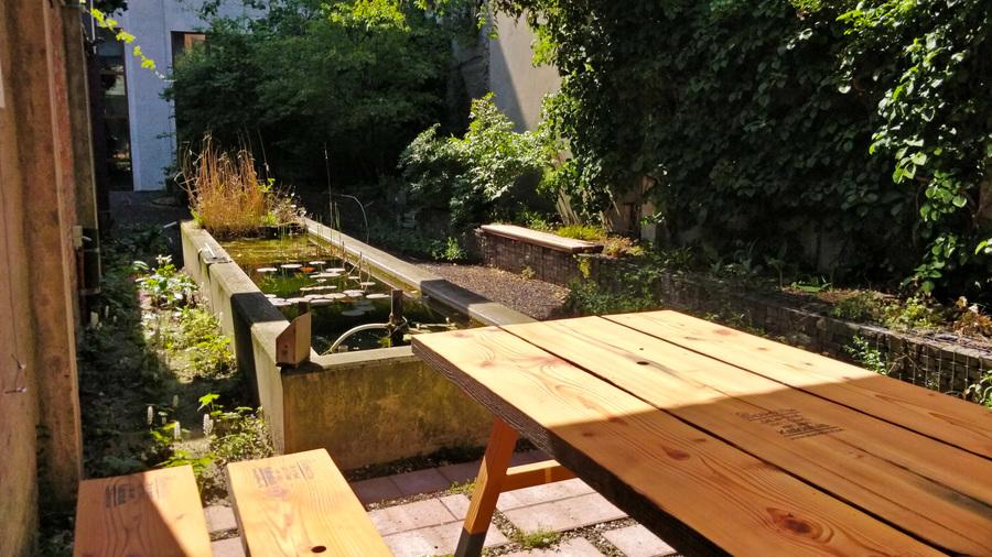 De tafels en banken staan op een terras, naast de vijver.