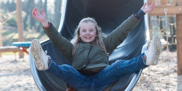 Een kind komt van een glijbaan in een speeltuin.