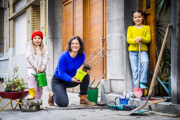 Een moeder en twee kinderen breken stenen uit en maken een geveltuintje