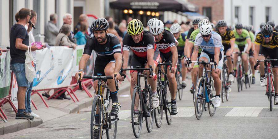 Verschillende amateurwielrenners fietsen door een straat in Antwerpen.