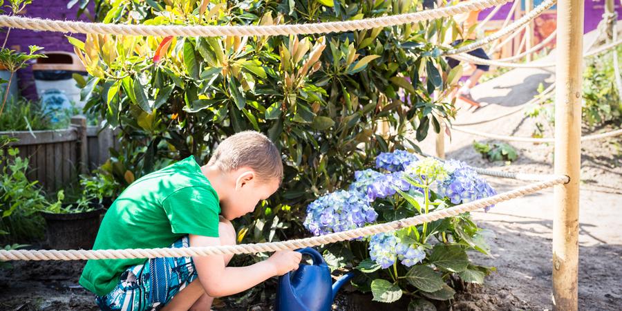 Jongen geeft plantjes water achter afbakening van de plantzone met palen en touw