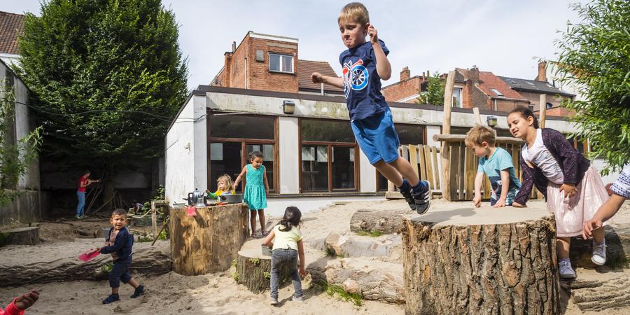 Jongen springt van boomstamschijf