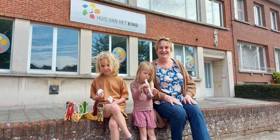 Speelgoedbende-vrijwilliger Martine zit met enkele kinderen voor het Huis van het Kind in Wilrijk.
