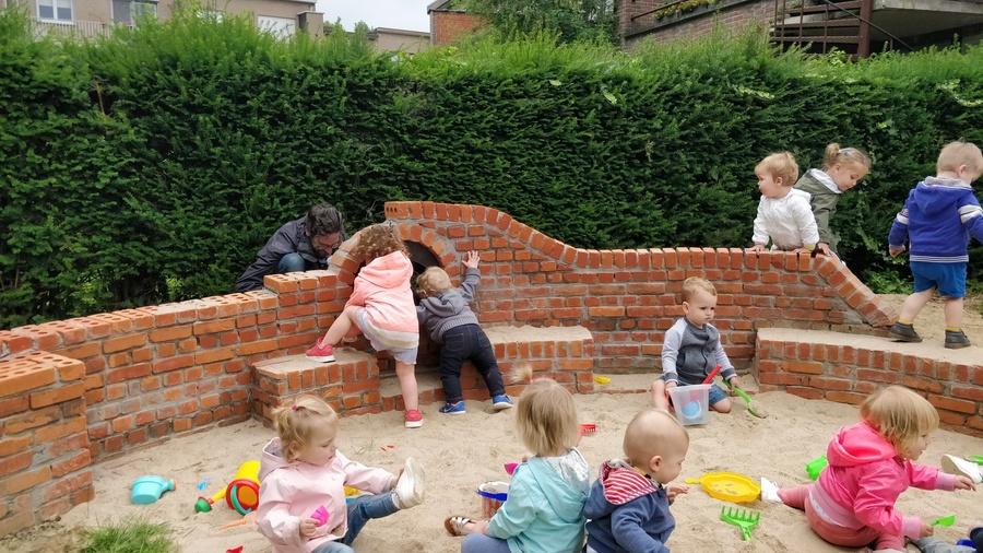 Kinderen kijken door kijkgaatje in de tengelmuur