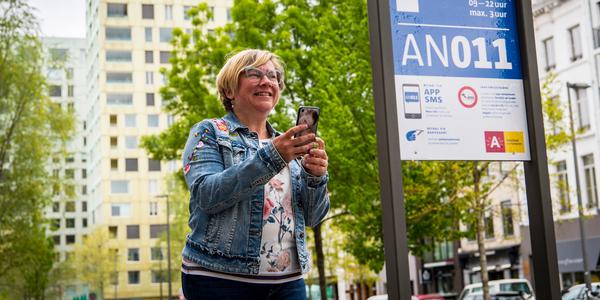 Vrouw met gsm voor een parkeerinformatiebord