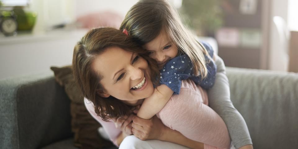 Een moeder en haar dochter lachten en knuffelen in de zetel.