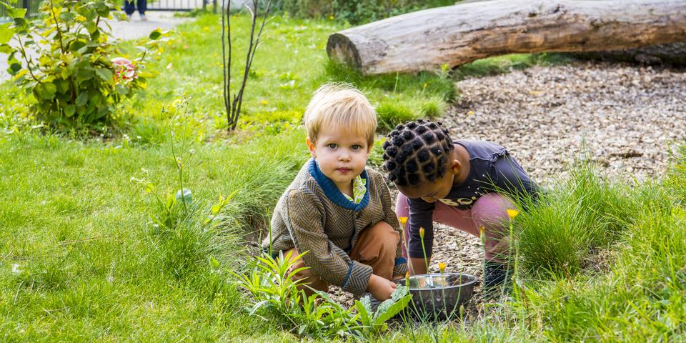 Twee kinderen spelen in de natuurlijke buitenruimte van kinderdagverblijf Brabbel